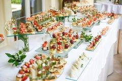 catering Av-plats mat Knuffa omkring tabellen med olika canapes, smörgåsar, hamburgare och mellanmål arkivfoton