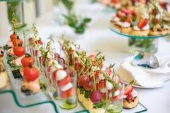 catering Av-plats mat Knuffa omkring tabellen med olika canapes, sm?rg?sar, hamburgare och mellanm?l fotografering för bildbyråer