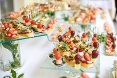 catering Av-plats mat Knuffa omkring tabellen med olika canapes, sm?rg?sar, hamburgare och mellanm?l arkivbilder