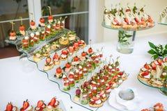 catering Av-plats mat Knuffa omkring tabellen med olika canapes, sm?rg?sar, hamburgare och mellanm?l royaltyfria foton