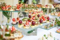 catering Av-plats mat Knuffa omkring tabellen med olika canapes, sm?rg?sar, hamburgare och mellanm?l arkivfoton