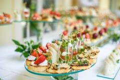 catering Av-plats mat Knuffa omkring tabellen med olika canapes, sm?rg?sar, hamburgare och mellanm?l royaltyfri fotografi