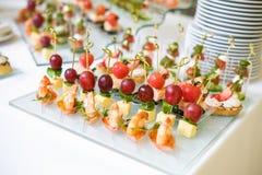 catering Av-plats mat Knuffa omkring tabellen med olika canapes, sm?rg?sar, hamburgare och mellanm?l arkivfoto