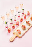 Catering, banquet, party food concept over pastel pink background Stock Image