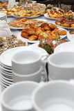 Catering banquet table with baked food snacks, sandwiches, cakes, cups and plates Stock Photos