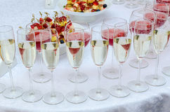 Catering bar for celebration. Interior for wedding day. Champagne in the glases on the buffet table. Canapes with strawberry Stock Photography