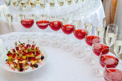 Catering bar for celebration. Interior for wedding day. Champagne in the glases on the buffet table. Canapes with strawberry Stock Image