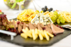 Catering buffet cheese plate with pate. Catering buffet cheeseboard and pate, grapes and walnuts cheeseboard Royalty Free Stock Image