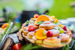 Catering buffet food outdoor. Cakes colorful fresh fruits berries oranges grapes and herb decorations Royalty Free Stock Image