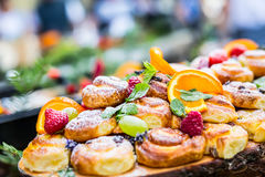 Catering buffet food outdoor. Cakes colorful fresh fruits berries oranges grapes and herb decorations Royalty Free Stock Photos