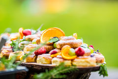 Catering buffet food outdoor. Cakes colorful fresh fruits berries oranges grapes and herb decorations Stock Photos