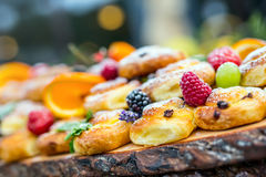 Catering buffet food outdoor. Cakes colorful fresh fruits berries oranges grapes and herb decorations.  Stock Photo
