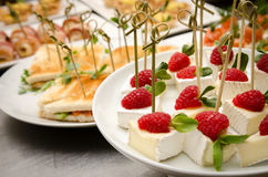 Catering buffet table with a brie cheese skewers with raspberry. Catering buffet table with a delicious food Stock Photography