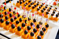 Catering canape cheese olives. White plate Stock Photo