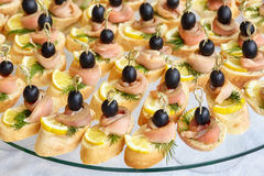 Catering of canape with olives, lemon and salmon Royalty Free Stock Image