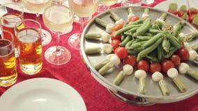 catering De samenstelling van bloemen, groenten op de schotels en dranken in glazen stock video
