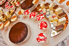Catering desserts. Table filled with different types of desserts, such as cakes, cookies, tiramisu, cream topped with syrup Royalty Free Stock Image