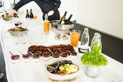 Catering Desserts on Buffet Table with Man Serving Wine in the B royalty free stock photos