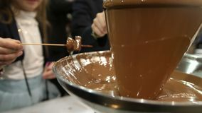Catering on event - chocolate fountain people use chocolate fountain with fruit stick stock video footage