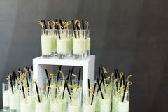 Catering finger food, cold soup in glasses with straws. stock photo