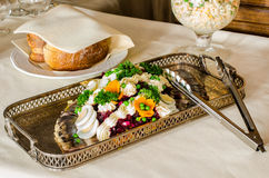 Catering food in silver dish. Herring dish in silver dish, in background bread and white salad royalty free stock photography