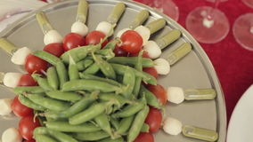 Catering. On a large tray canapes with tomatoes, mozzarella and sauce, in the center of the tray pea pods stock footage