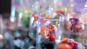 Catering for Party. Close up of appetizers with cherry tomatoes, green olives, olive oil, cheese and spices in short glasses on wood brown table. Horizontal stock video