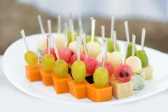 Catering for party. Close up of appetizers with watermelon, grapes, melon, kiwi, cheddar, parmesan, blue cheese over white plate. Selective focus royalty free stock photography