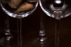 Catering, party concept: close-up image of empty wine glass and a glass filled with wine corks on a dark wooden background. Select Royalty Free Stock Images