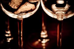 Catering, party concept: close-up image of empty wine glass and a glass filled with wine corks on a dark wooden background. Select Stock Images