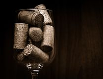 Catering, party concept: close-up image of wine glass with corks on a dark wooden background. Selective focus Stock Image
