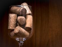 Catering, party concept: close-up image of wine glass with corks on a dark wooden background. Selective focus. Stock Image