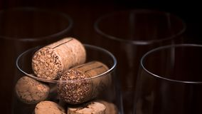 Catering, party concept: close-up image of wine glass with corks and empty glasses on a dark wooden background. Selective focus Royalty Free Stock Photos