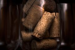Catering, party concept: close-up image of wine glass with corks and empty glasses on a dark wooden background. Selective focus. Stock Photos
