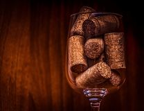 Catering, party concept: vintage close-up image of wine glass with corks on a dark wooden background. Selective focus Stock Photo