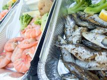 Catering portions of fish and other seafood served with boiled vegetables. Catering portions of fish and other seafood served with assorted boiled vegetables Stock Photo