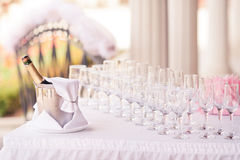 Catering service. Bottle of champagne in bucket with glasses Stock Photos