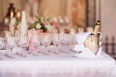 Catering service. Bottle of champagne in bucket with glasses Stock Images