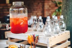 Catering service. Business, catering service. Drinks on summer party. Catering table with trendy glasses, big bottle of lemonade o. R cocktail for outdoor party stock photo