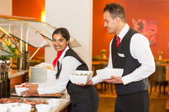 Catering service employees filling buffet in restaurant Stock Photos