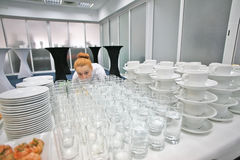 Catering service of events. Redhead cute waitress in a white shirt is checking water in  glasses on the table. Catering service, breakfast in the hotel, coffee Stock Photography