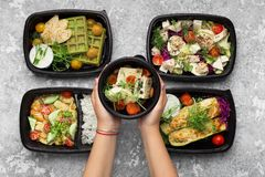 Plastic containers with delicious food on gray background. Catering service menu presentation. Woman serving plastic containers with take away meals, top view royalty free stock photo
