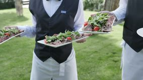 Catering service two waiters in their hands hold tomato salami sausage meat dishes to celebrate a wedding or event slow. Motion stock footage