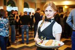 Catering service. waitress on duty. Catering service. Restaurant waitress girl with food tray at event. Natural authentic shot in challenging light condition Royalty Free Stock Photography