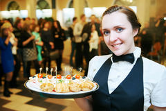 Catering service. waitress on duty. Catering service. Restaurant waitress girl with food tray at event. Natural authentic shot in challenging light condition Stock Photo
