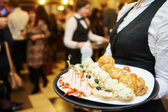 Catering service. waitress on duty. Catering service. Restaurant waitress girl with food tray at event. Natural authentic shot in challenging light condition Royalty Free Stock Image
