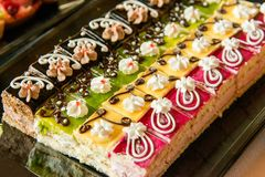 Catering sweets, closeup of various kinds of cakes on event or wedding reception. Selective focus royalty free stock photo
