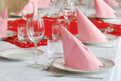 Catering table arranged with silverware and pink napkins Stock Photography