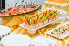 Catering table with dishes and snacks on the business event in the hotel hall. Service at business meeting, party, weddings. Selec Stock Photos