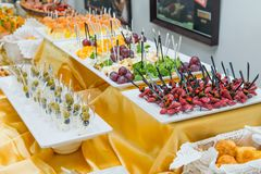Catering table with dishes and snacks on the business event in the hotel hall. Service at business meeting, party, weddings. Selec Stock Photography